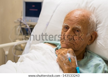 Elderly 80 plus year old man recovering from surgery in a hospital bed. - stock photo