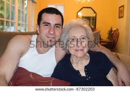 Elderly 80 plus year old woman with Alzheimer and her grandson in a home setting. - stock photo