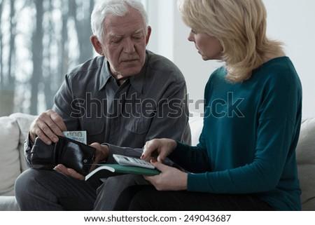 Elderly poor couple counting money - stock photo