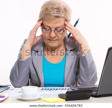 Elderly senior business woman holding hand on her head and analyzing financial charts at desk in office, analysis of sales plan, business report - stock photo