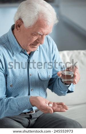 Elderly sick man taking the pills - stock photo