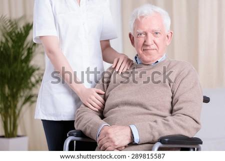 Elderly smiling man on wheelchair and his nurse - stock photo