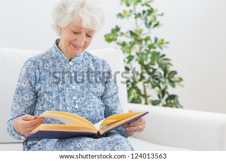Elderly smiling woman looking at photos on a sofa - stock photo