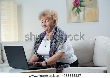 Elderly smiling woman using her black laptop - stock photo