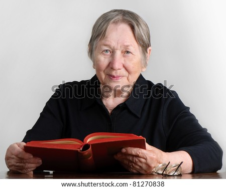 Elderly smiling woman with book - stock photo