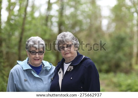 Elderly twin sisters enjoying a walk in a woodland - stock photo
