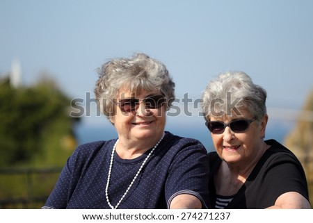 Elderly twin sisters on holiday - stock photo