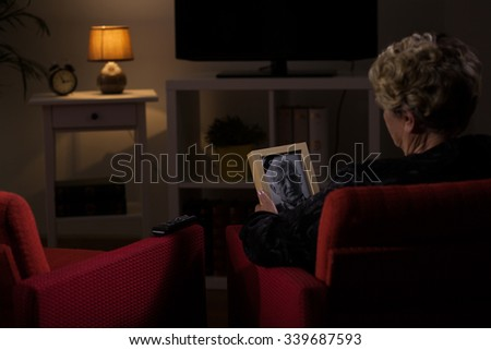 Elderly widow thinking about her dead husband  - stock photo