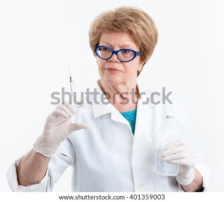 Elderly woman a doctor looking at a syringe for vaccination in her hand, white background - stock photo