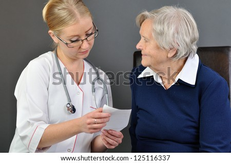 Elderly woman and a young doctor. - stock photo