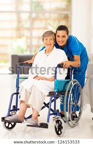 elderly woman and young caregiver at home - stock photo