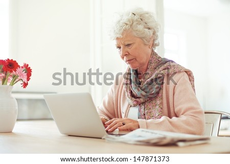 Elderly woman at home typing something using her laptop - stock photo