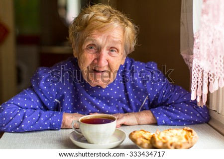 Elderly woman drinking tea with buns sitting in the kitchen of his home. - stock photo