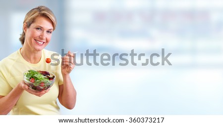 Elderly woman eating salad. - stock photo