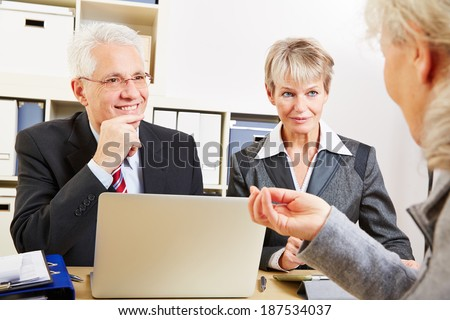 Elderly woman getting financial consultation in a bank - stock photo