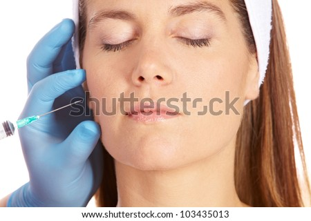 Elderly woman getting wrinkles removed in her cheeks with syringe - stock photo