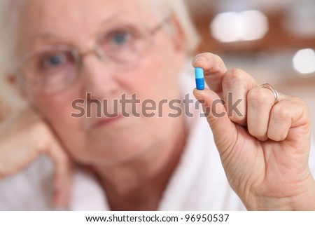 Elderly woman holding a capsule between her fingers - stock photo