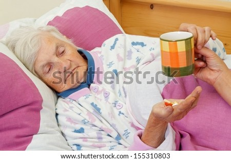 Elderly woman holding a cup of tea and her medicine - stock photo