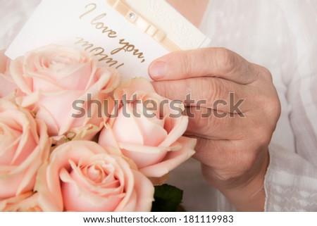 Elderly woman holding bouquet of roses. Mother's day background  - stock photo
