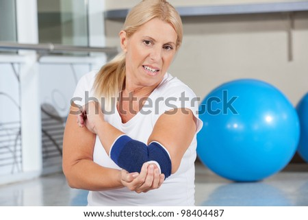 Elderly woman holding her aching elbow with bandage in gym - stock photo