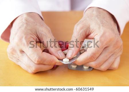 elderly woman holding pills - stock photo