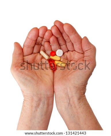 Elderly woman holding pills in her hands - stock photo