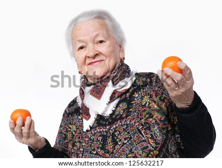 Elderly woman holding two tangerines in her hand against white background - stock photo