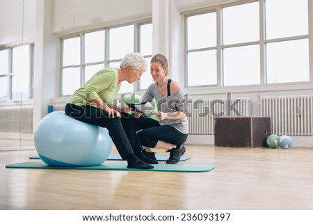 Elderly woman in a gym sitting on exercise ball and talking to her personal female trainer about exercise plan. Senior woman and coach looking at health report together. - stock photo