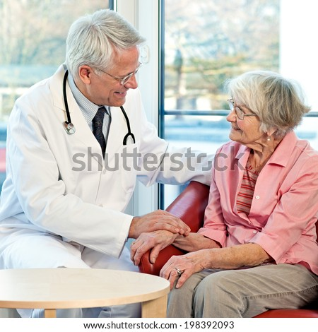 Elderly woman in consultation with her doctor sitting talking to him in an armchair in front of a window smiling at his sympathetic kindly approach - stock photo