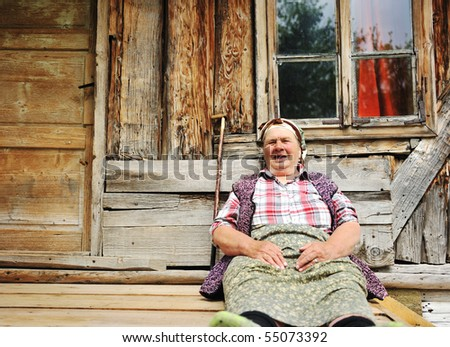 Elderly woman in front of her old house - stock photo