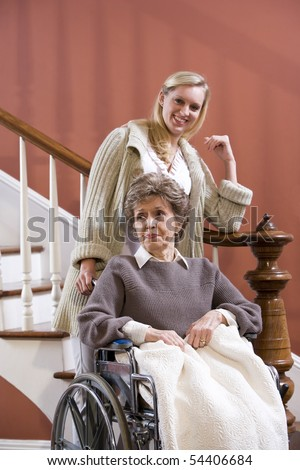 Elderly woman in 70s in wheelchair at home with nurse - stock photo