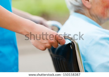 Elderly woman in wheelchair pushed by nurse's hands. - stock photo