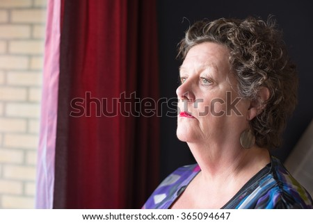 Elderly woman looking out window. Older woman. Sad. Senior woman. Old lady. - stock photo