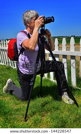 Elderly woman looking through her viewfinder to capture that perfect shot. - stock photo