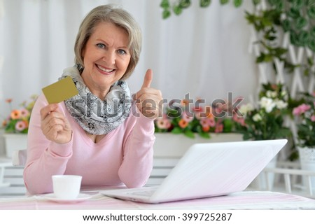 elderly woman making purchases on the internet while sitting at the table - stock photo