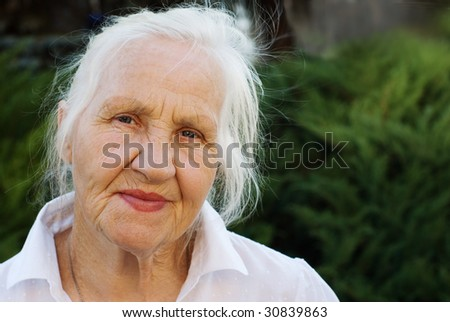 Elderly woman on a green background - stock photo