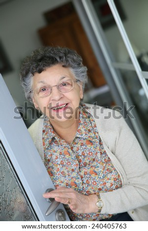Elderly woman opening home entrance door - stock photo