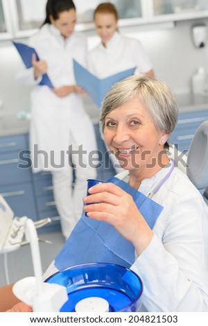 Elderly woman patient dentist team sitting chair at dental surgery - stock photo