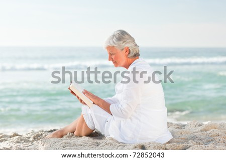 Elderly woman reading her book on the beach - stock photo