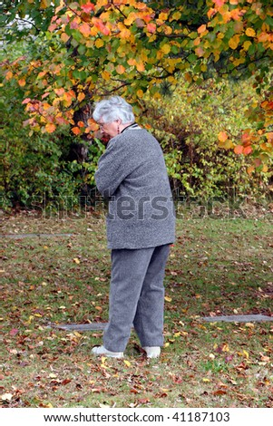 elderly woman remember honor in autumn cemetery - stock photo