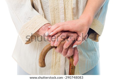 Elderly woman's hands holding a wooden walking stick with a consoling young hand. - stock photo