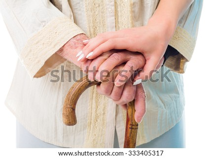 Elderly woman's hands on a wooden walking stick held by a consoling young hand. - stock photo