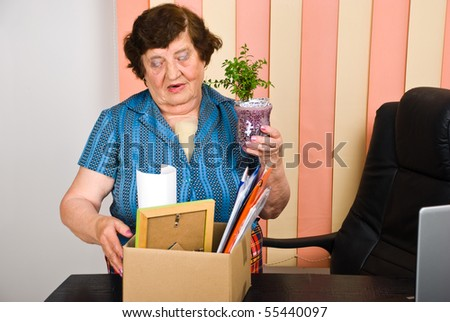 Elderly woman 80s years retired from activity,she holding a box with her goods and leave the office - stock photo