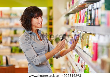 Elderly woman scanning barcode of cosmetics product in a drugstore - stock photo