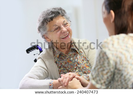 Elderly woman sharing good time with home carer - stock photo