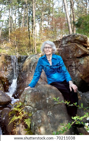Elderly woman sits besides waterfall at Garvin Woodland Garden in Hot Springs, AR.  She is wearing a vivid blue shirt. - stock photo