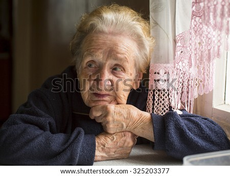 Elderly woman sitting at table in the house. - stock photo