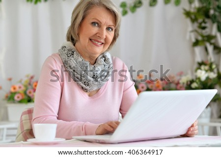 elderly woman sitting at the computer with a cup - stock photo