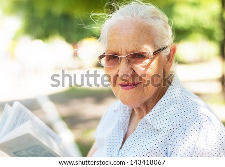 Elderly woman sitting in a garden and reading a book - stock photo