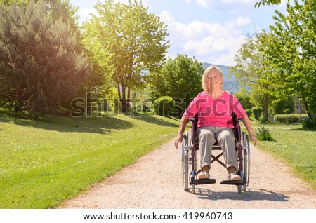 Elderly woman smiles while seated in wheel chair on a beautiful summer day rolling down a rocky park path - stock photo